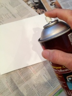 Applying spray adhesive to the 8.5 x 11 paper