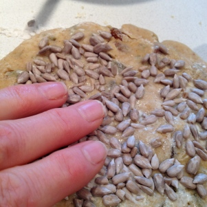 Patting raw sunflower seeds onto the disk