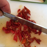 Chopping sun dried tomatoes preserved in olive oil