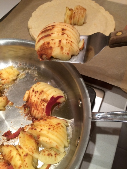 Transferring the cooked apples to the crust