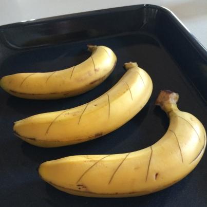Score the bananas and roast